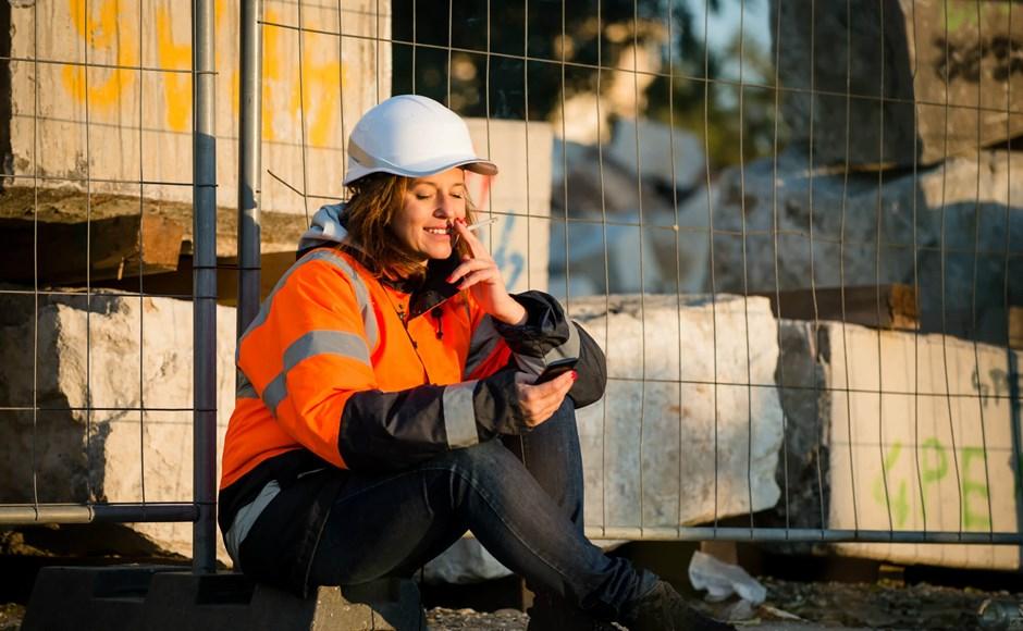 Worker looking at phone during smoke break