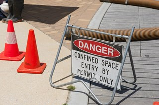 What risks need to be considered when rescuing someone from a confined space?
