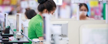 Grocery cashier wearing safety mask