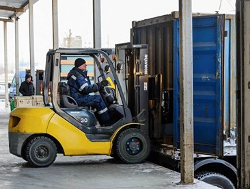 What kind of PPE is required when loading and unloading a docked trailer?