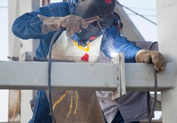 Should I use a protective jacket or an apron to stay safe during welding work?