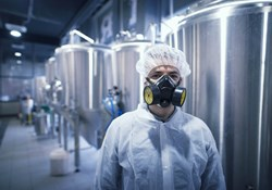 Industrial manufacturing worker wearing coveralls and respirator